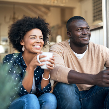 Couple drinking coffee on balcony | Creekstone Village