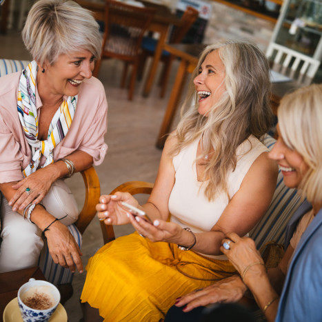 Women smiling and having coffee
